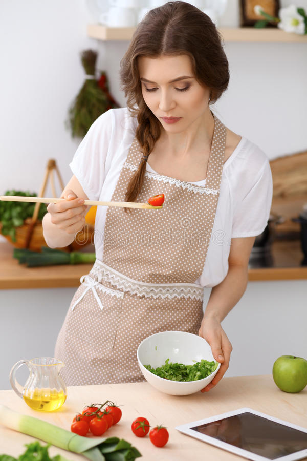 Young brunette woman is cooking and tasting fresh salad in the kitchen. Housewife holding wooden spoon in her hand stock photo