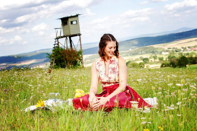 Young brunette woman in dirndl sitting in a field of flowers on a blanket. Portrait of young brunette woman in dirndl sitting in a field of flowers on a blanket stock photos