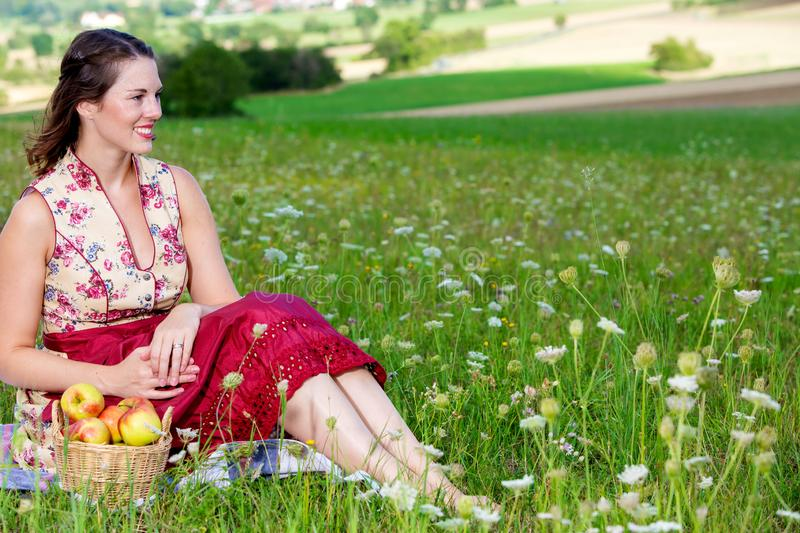 Young brunette woman in dirndl sitting in a field of flowers on a blanket. Portrait of young brunette woman in dirndl sitting in a field of flowers on a blanket royalty free stock image