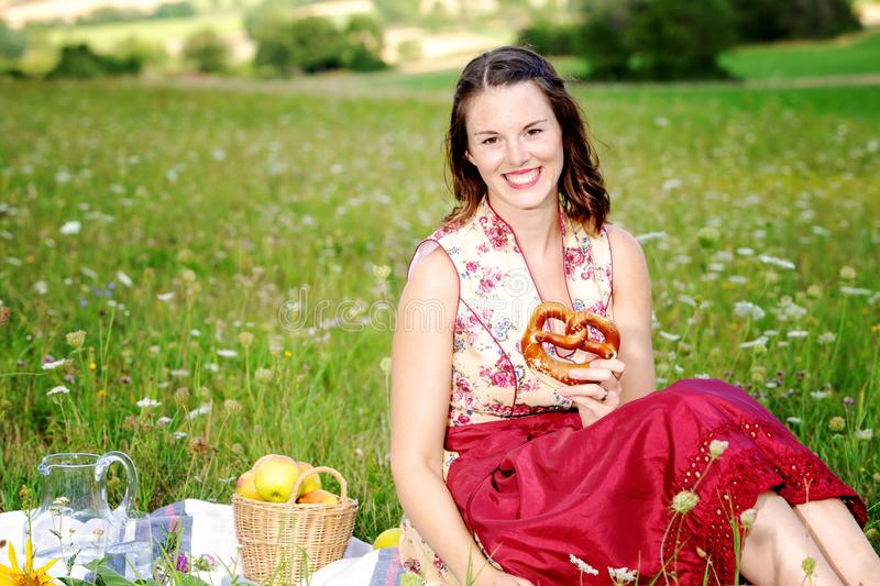 Young woman in dirndl sitting in a field of flowers and holding a pretzel. Young brunette woman in dirndl sitting in a field of flowers and holding a pretzel stock image