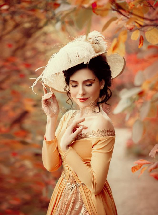 A young brunette woman with an elegant, hairstyle in a hat with a strass feathers. Lady in a yellow vintage dress walks through th. E autumn landscape. Artistic royalty free stock image