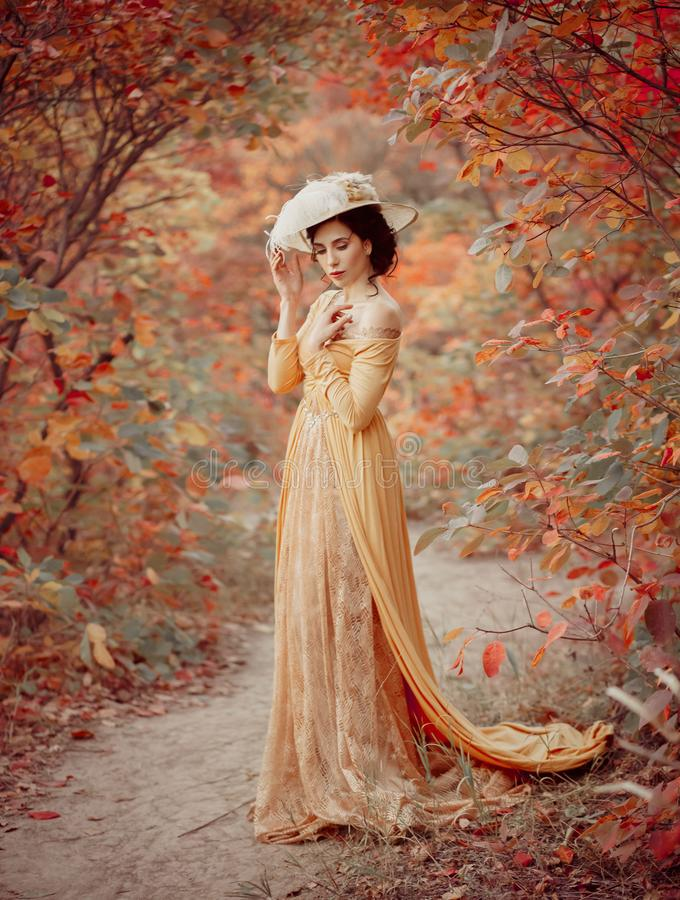 A young brunette woman with an elegant, hairstyle in a hat with a strass feathers. Lady in a yellow vintage dress walks. Through the autumn landscape. Artistic royalty free stock images