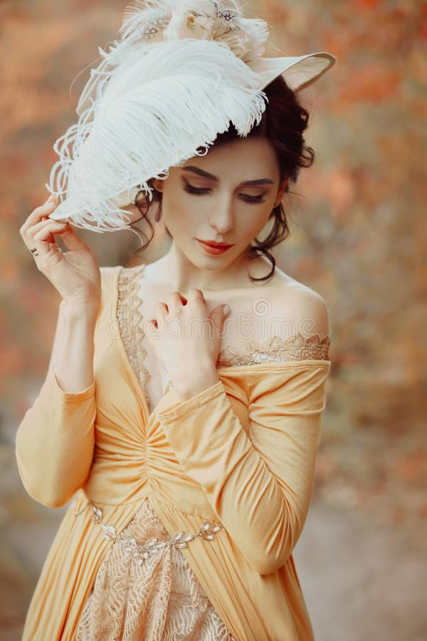 A young brunette woman with an elegant, hairstyle in a hat with a strass feathers. Lady in a yellow vintage dress walks. Through the autumn landscape. Artistic stock images