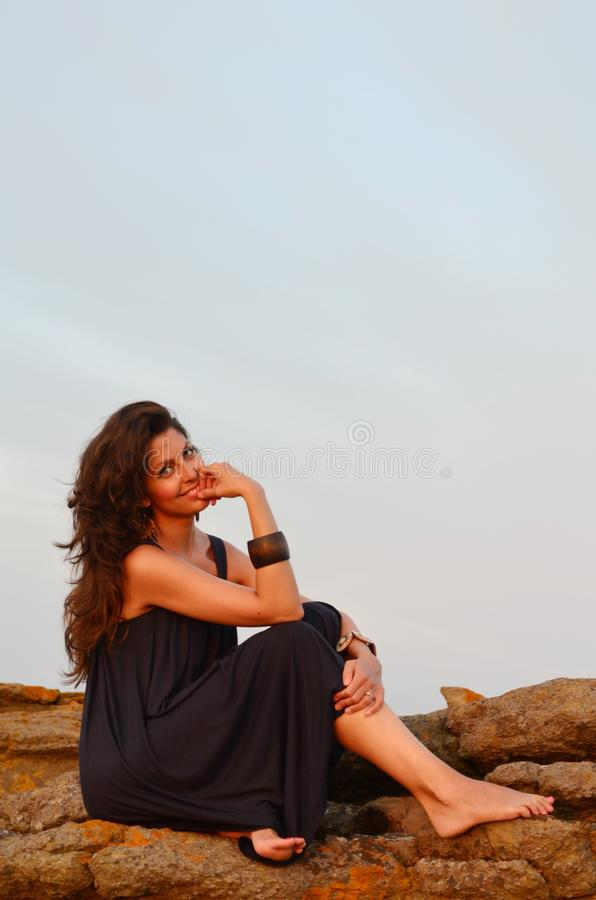 Beautiful Young Woman Sitting on a Rocks above the Sea stock image