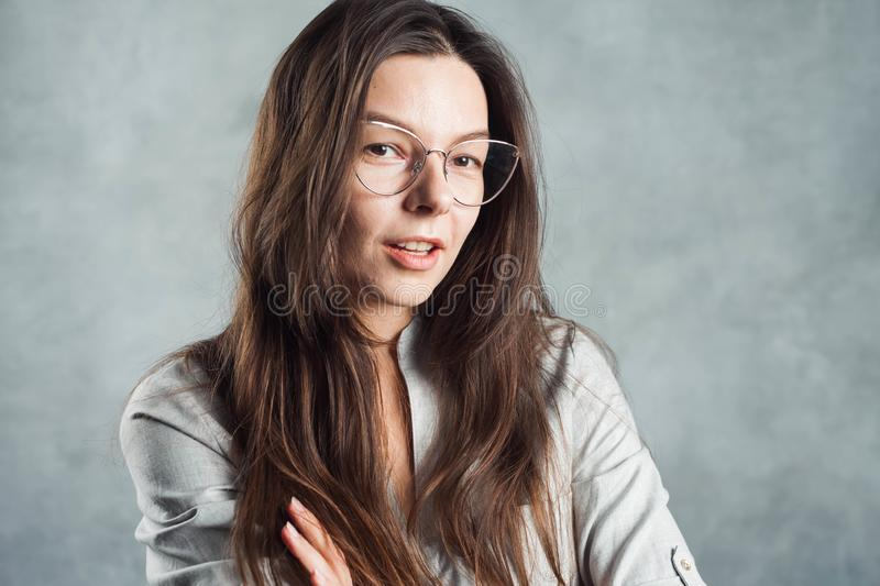 Young brunette woman in glasses, self-confidence. Smiling and calm girl stock photography