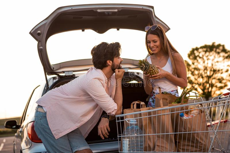 A young brunette woman has a pineapple in her hands and a shopping cart of groceries in paper bags. With her is her handsome stock photos