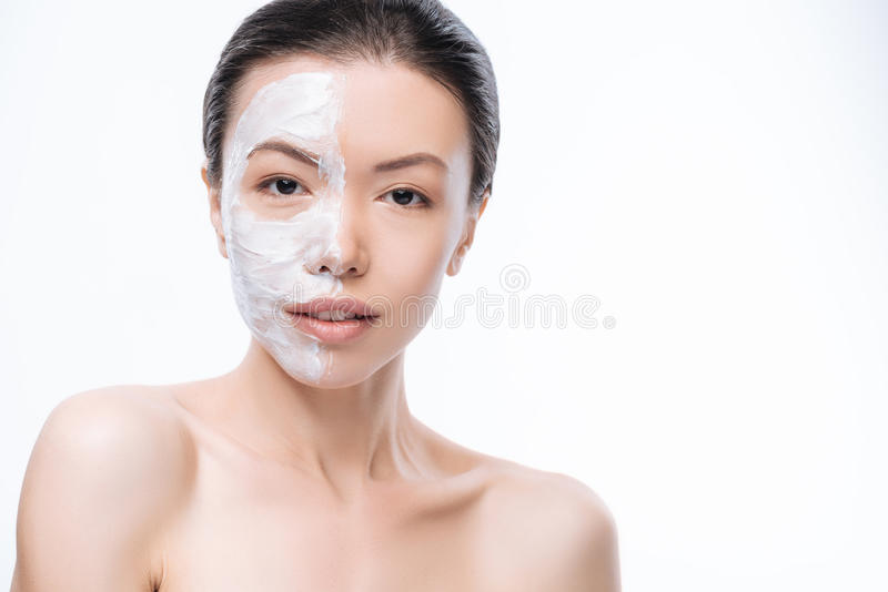Young brunette woman having cream on her face stock photography