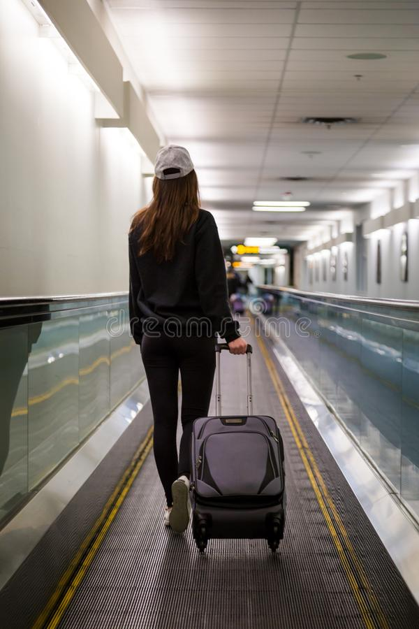 Young brunette woman with her luggage in an airport concourse. Young brunette woman with her luggage in an airport concourse royalty free stock image