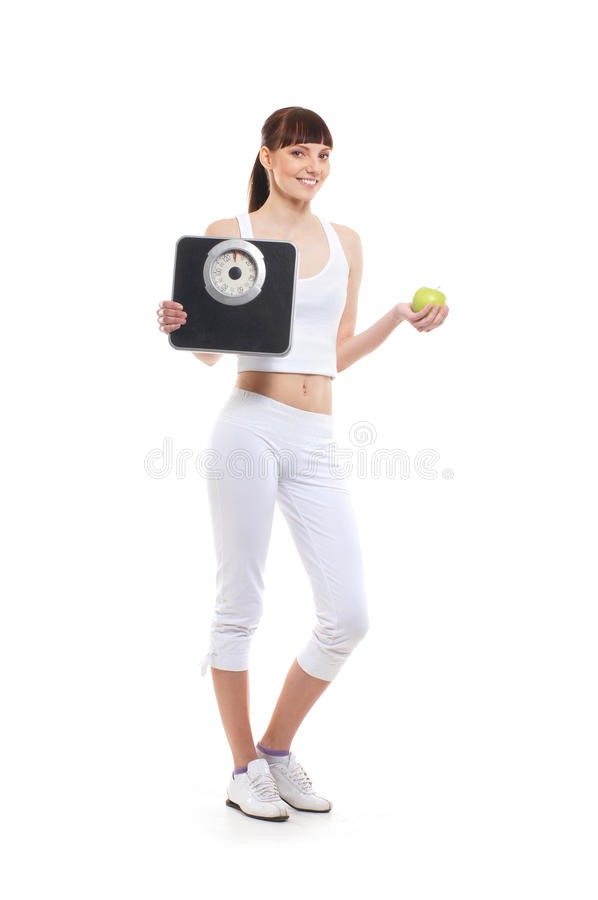 A young brunette woman holdin an apple and scales. A young and attractive brunette Caucasian woman is holdin a fresh green apple and black weight scales. The stock photography