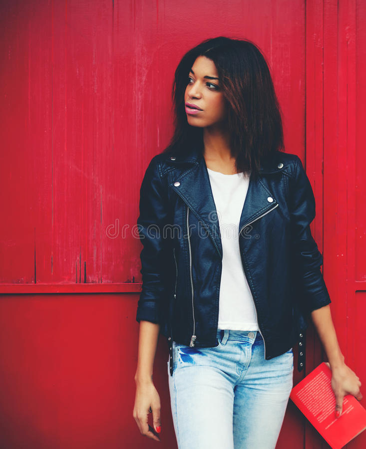 Young brunette woman holding book in the hand while strolling in the city at her recreation time. Attractive afro american female posing on red wall background stock photography