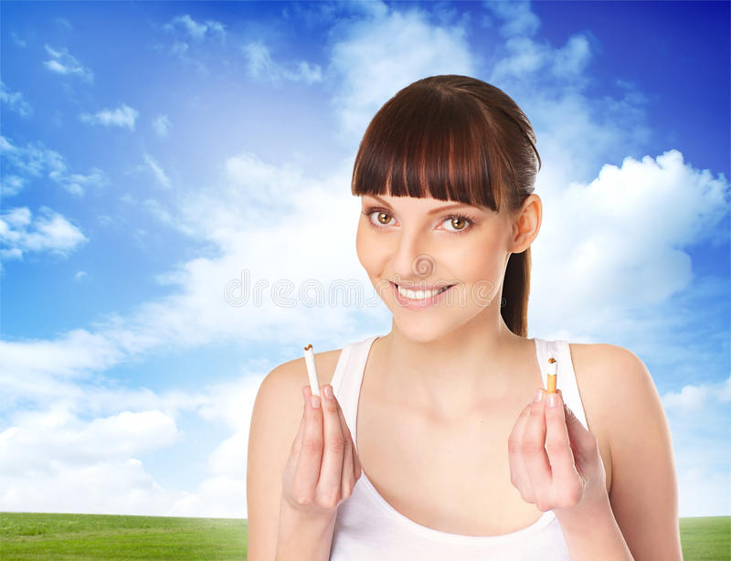 A young brunette woman holding a broken cigarette. A young and attractive brunette Caucasian woman holding a broken cigarette as an act against smoking. The royalty free stock photo