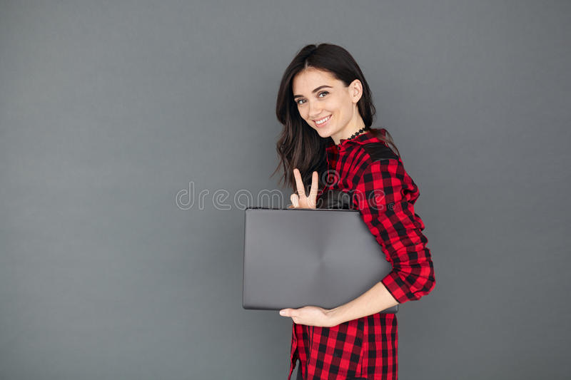 Young brunette woman holding laptop over grey background. Beautiful young brunette woman holding a laptop and smiling, looking at camera, over gray background stock photos