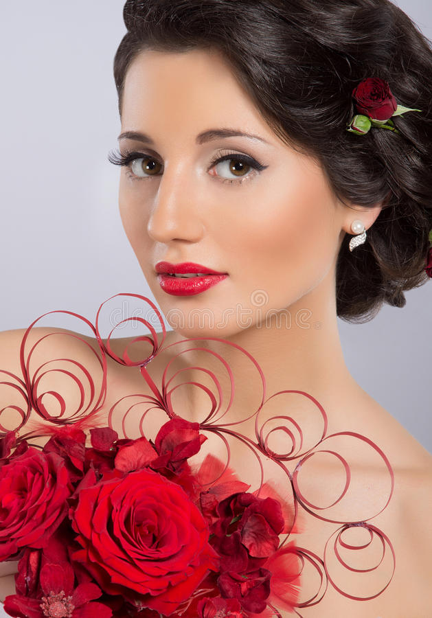 A young brunette woman holding red feathers stock image