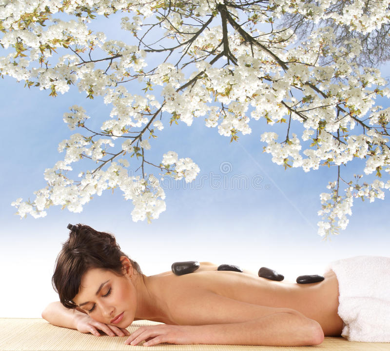 A young brunette woman laying on a spa procedure