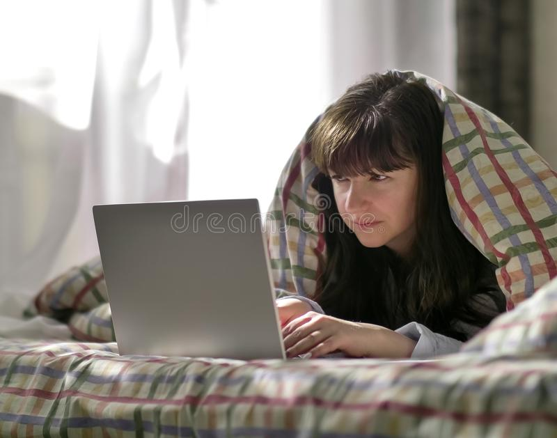A young brunette woman is lying under a blanket and typing in a laptop. Young brunette woman lies under the covers and looks into the laptop royalty free stock photography