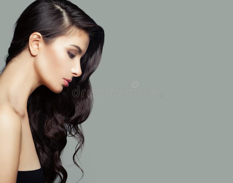 Young brunette woman with long perfect hairstyle. Hair care and beauty salon background.  royalty free stock photography
