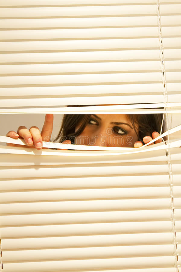 Download Young Brunette Woman Looking Through Window Blinds Stock Image - Image: 12355747