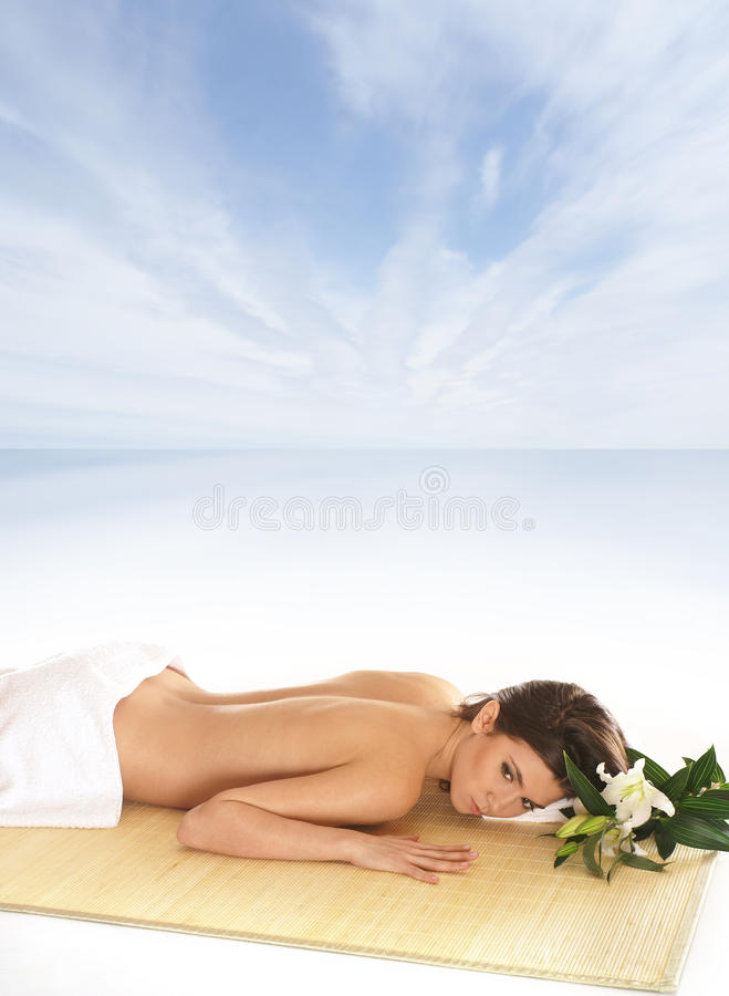 A young brunette woman is lying on a bamboo mat royalty free stock images