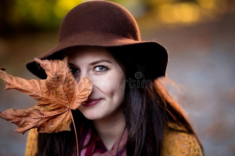 A young brunette woman with a maple leaf half covering her face. royalty free stock photo