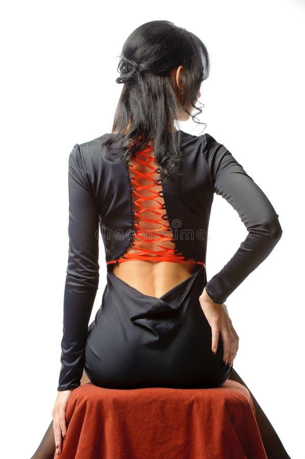 Young brunette woman in open-back black elegant dress sitting stock image