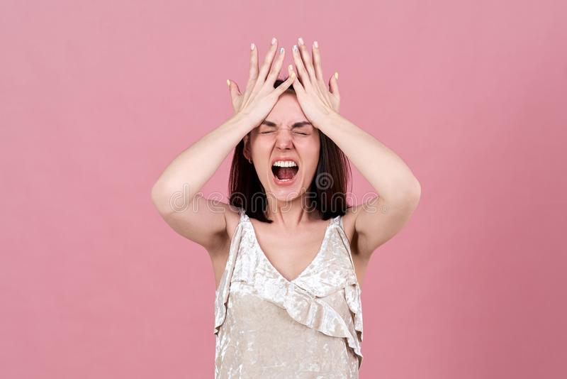 Young brunette woman in a rage screams, opening her mouth wide and pressing her palms to her forehead. royalty free stock photos