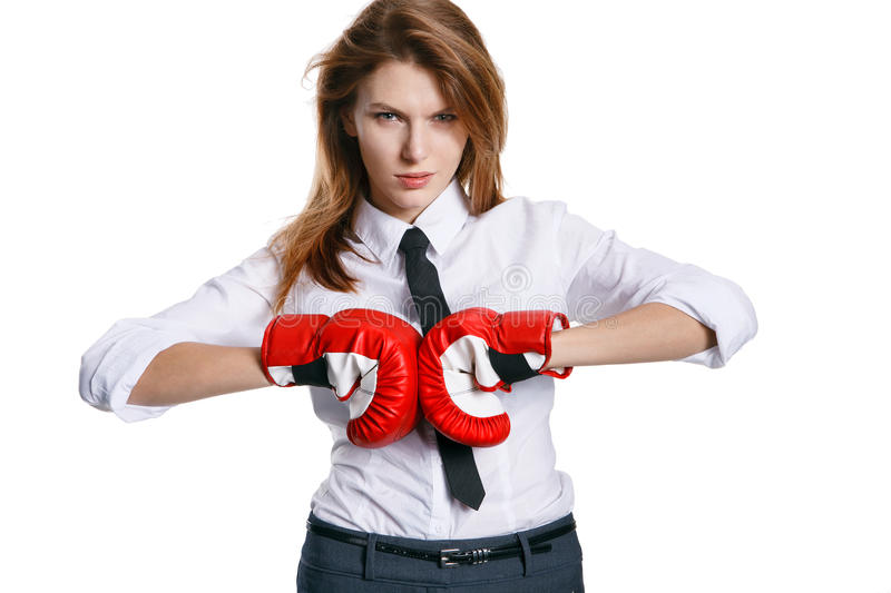 Young brunette woman is ready to resist the pressure. Businesslike person in a white shirt with red boxing gloves on a white background royalty free stock image