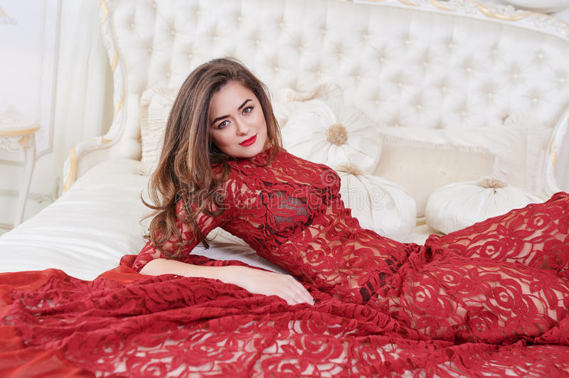 Young brunette woman in red dress lying on bed stock photography