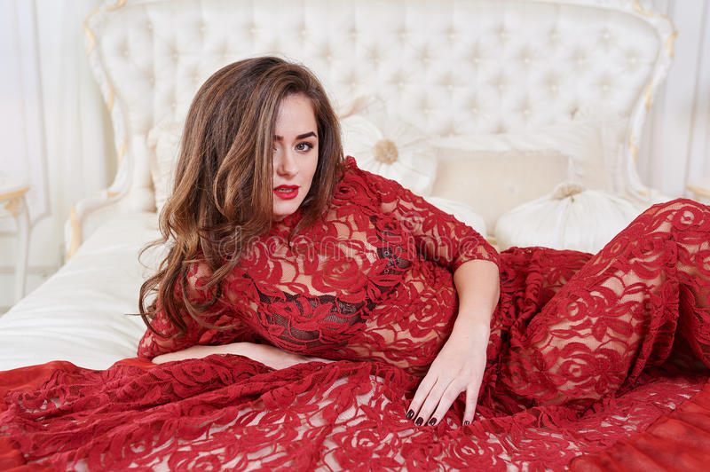 Young brunette woman in red dress lying on bed stock images
