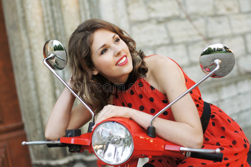 Download A Young Brunette Woman In A Red Dress On A Scooter Stock Photo - Image: 25998128