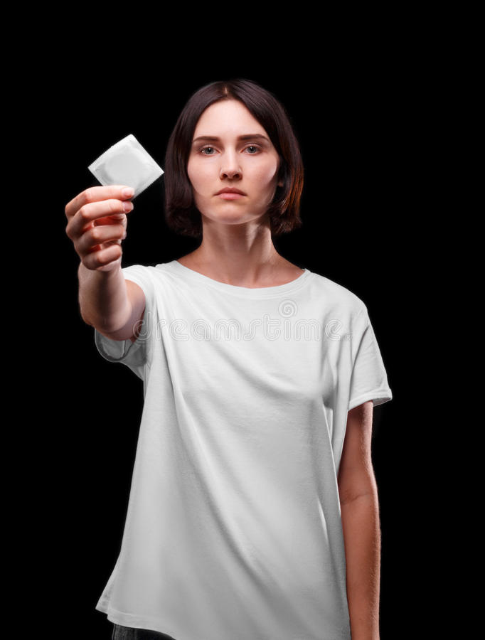 A serious young woman showing a packed condom on a black background. Healthy lifestyle concept. Copy space. stock photo