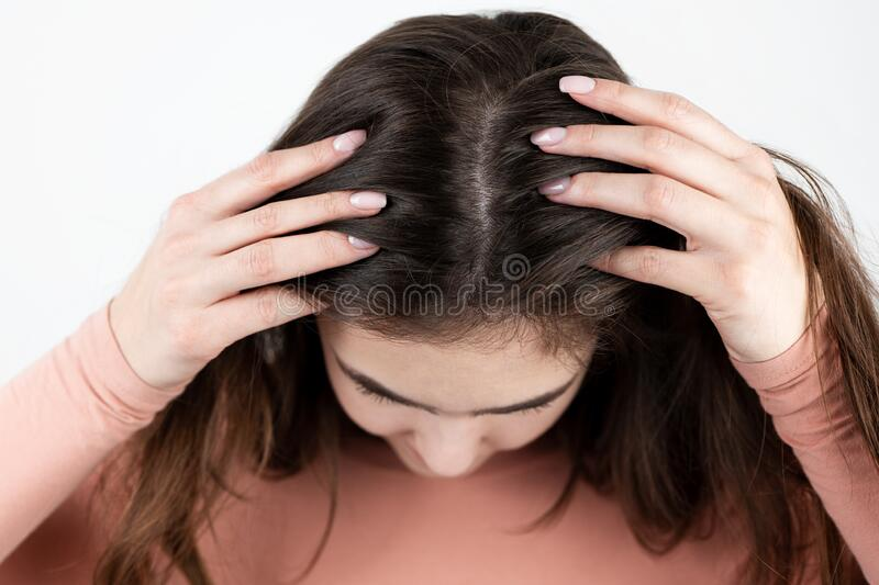 Young brunette woman showing her scalp, hair roots, color, grey hair, hair loss or dry scalp problem.  stock images