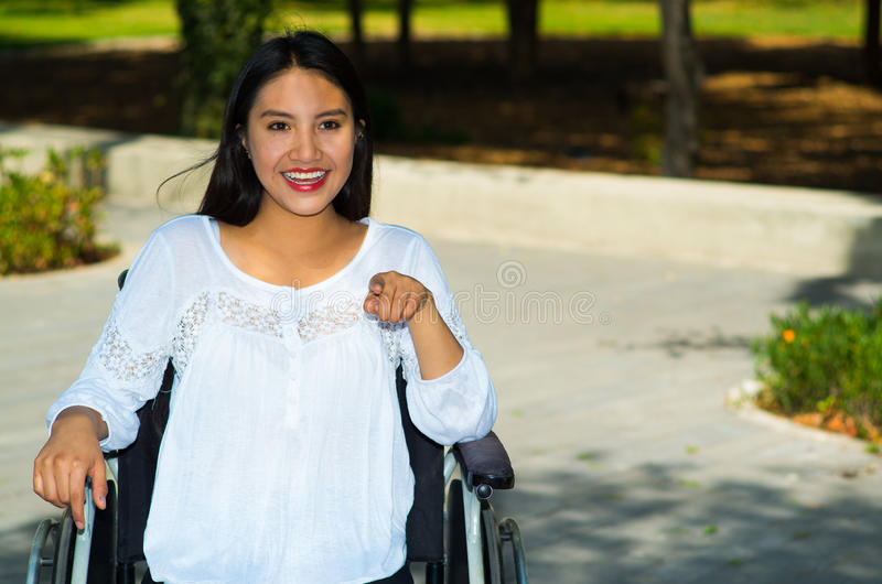 Young brunette woman sitting in wheelchair smiling with positive attitude, outdoors environment, physical recovery royalty free stock images