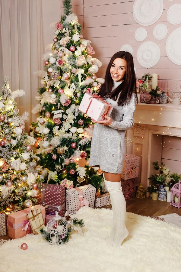 Young brunette woman smiling with the Christmas gift near Christmas tree royalty free stock photo