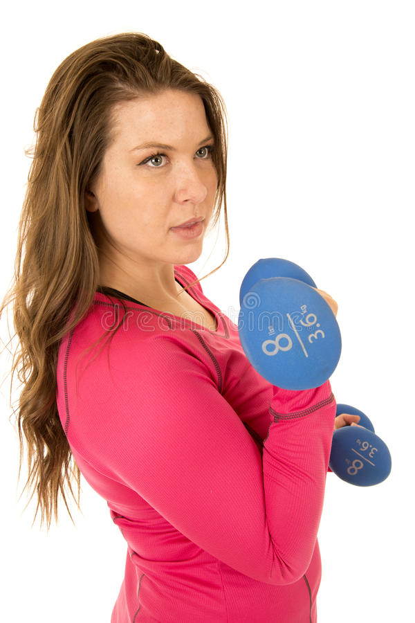 Young brunette woman standing holding blue barbells pumping iron stock photos
