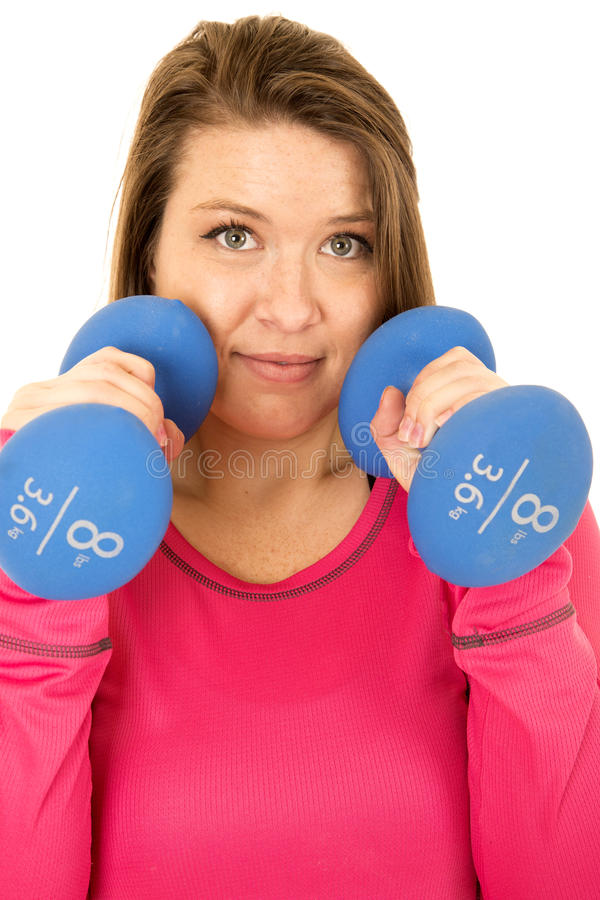 Young brunette woman standing holding blue 8 pound barbells no smile stock image