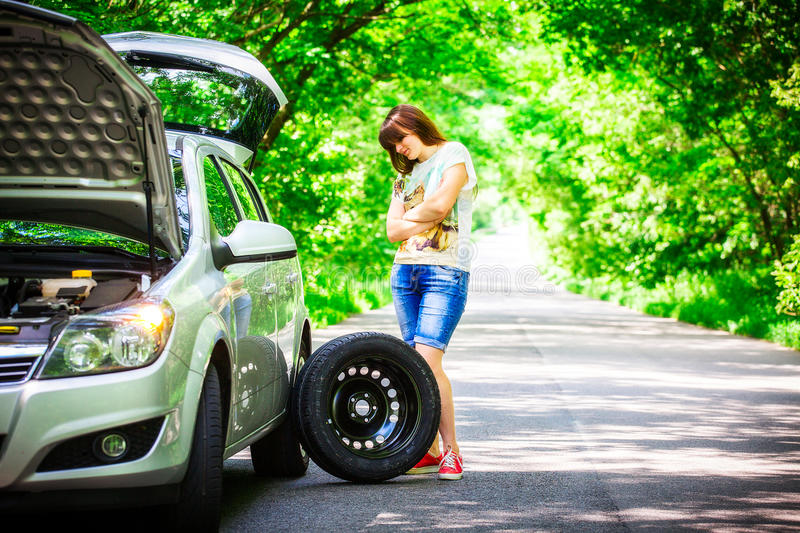 Young brunette woman stands near a silver car on the roadside with a broken wheel.  stock images