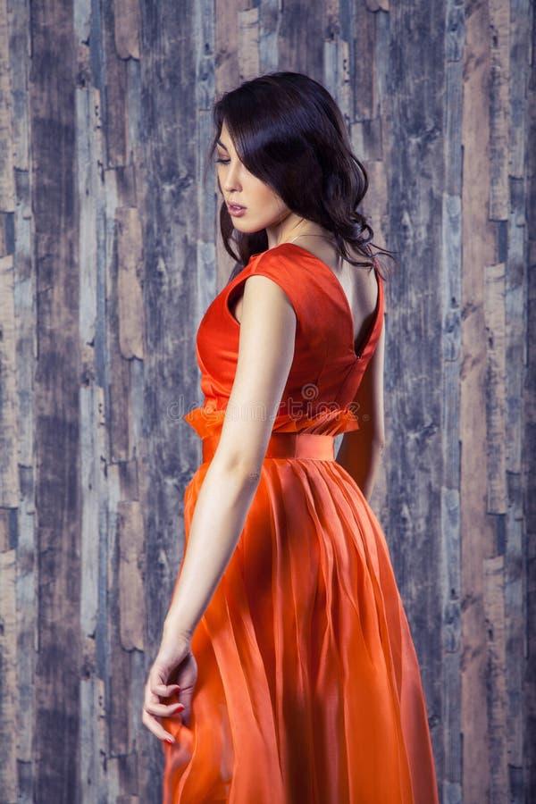 Young brunette woman in stylish orange silk dress posing on wood stock image