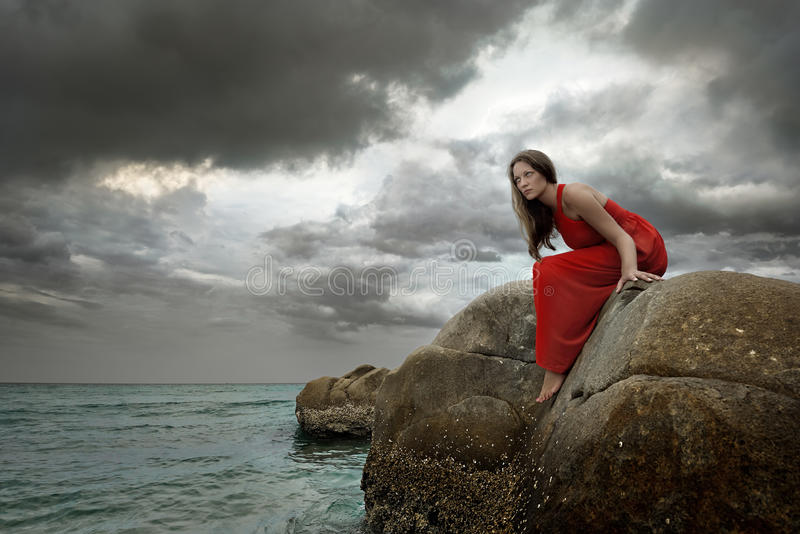 Young brunette woman in summer red dress sits on stone. And looking to the sea on the background dramatic of clouds royalty free stock image