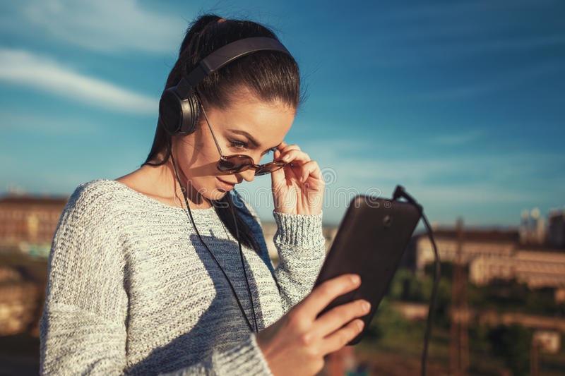 Young brunette woman take off sunglasses to view tablet outdoor royalty free stock photography