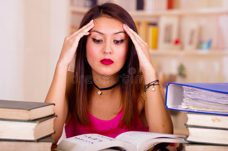 Young brunette woman wearing pink top sitting by desk with stack of books placed on it, holding hands onto head, tired royalty free stock photo