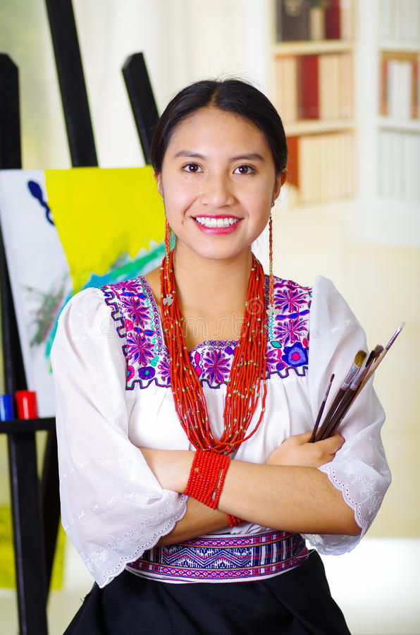 Young brunette woman wearing traditional andean clothing, holding paint brushes and posing, canvas behind, inside studio royalty free stock photos