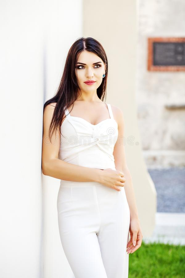 Young brunette woman in white clothes. The concept of fashion an royalty free stock photos