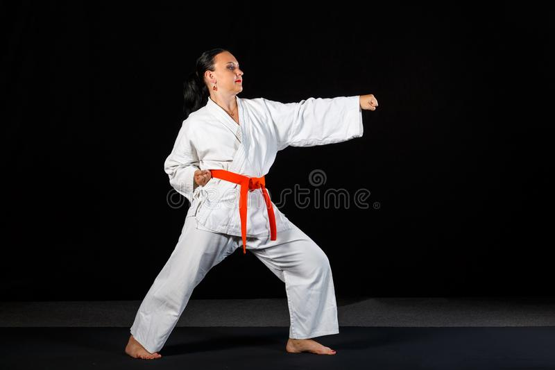 A young brunette woman in a white kimono doing karate on a black background in full growth. Horizontal frame royalty free stock photography