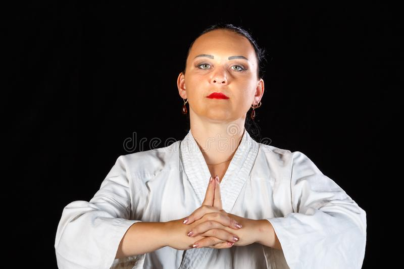 A young brunette woman in a white kimono is engaged in karate on a black background. Horizontal photo stock photos