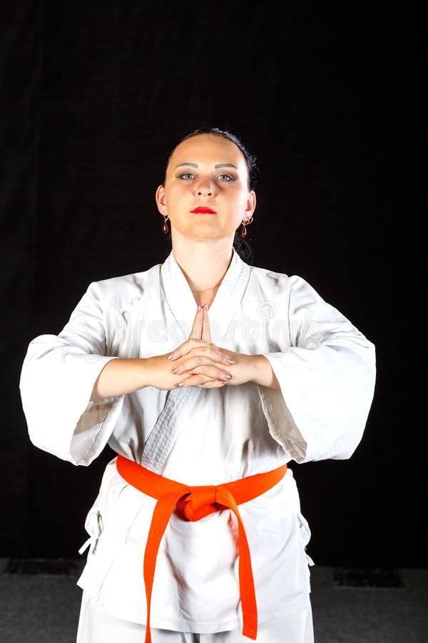 A young brunette woman in a white kimono is engaged in karate on a black background. Vertical frame royalty free stock photos