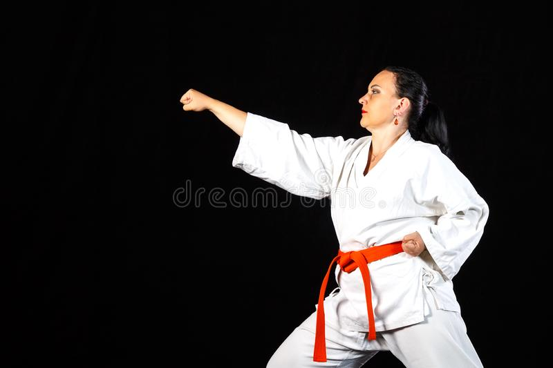 A young brunette woman in a white kimono is engaged in karate on a black background. Horizontal photo royalty free stock photos