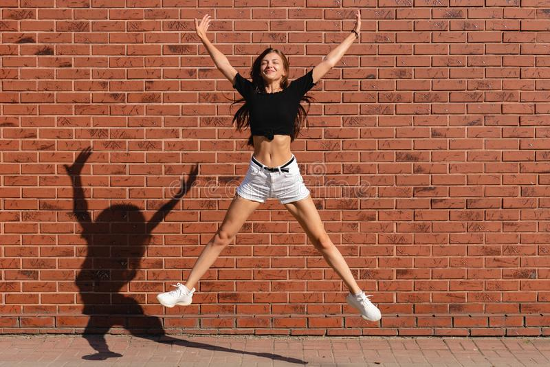 Young brunette woman in white shorts and black top jump in star shaped with closed eyes, red brick wall on the. Background, outdoor photo royalty free stock image