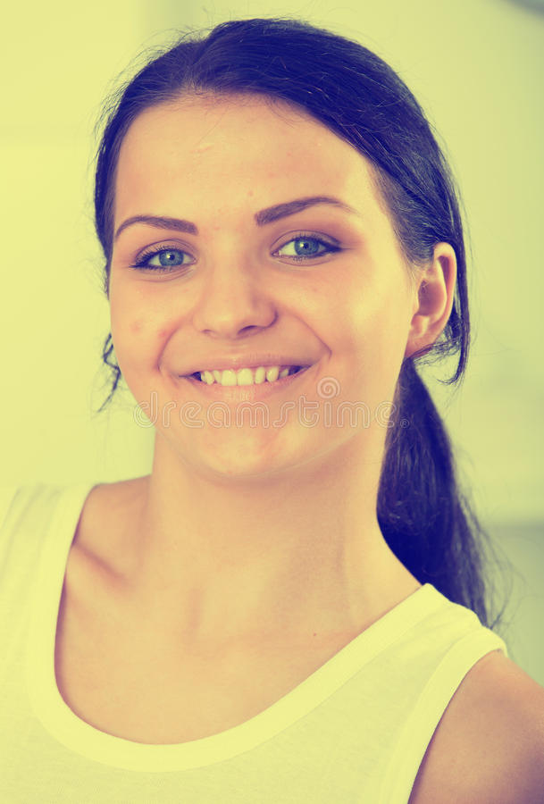 Young brunette woman in white. Standing in room and smiling royalty free stock image