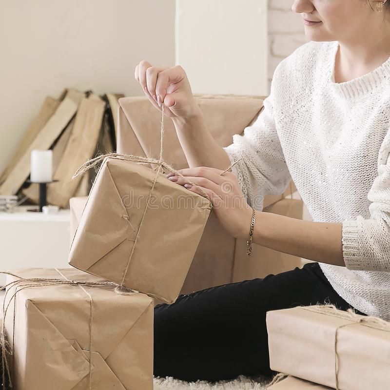 A young brunette woman in a white sweater is sitting on the floor in a bright room and examining boxes of gifts. In craft paper.girl opens a box with gifts royalty free stock images