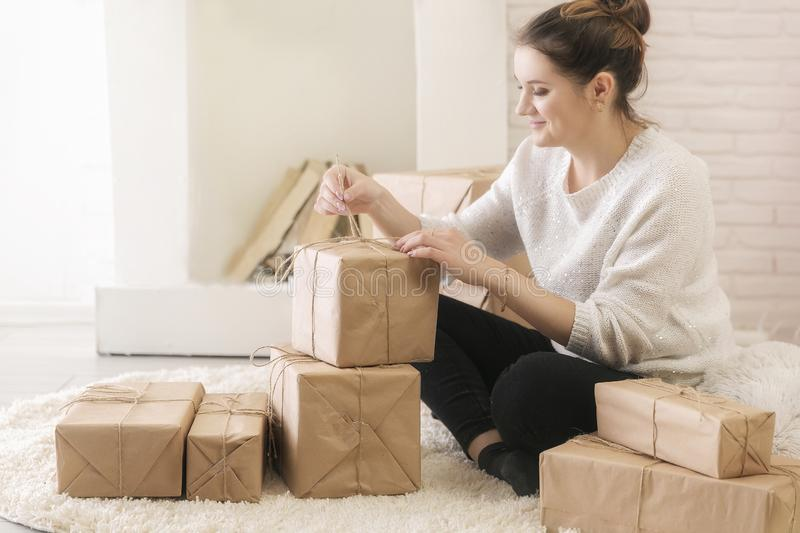 A young brunette woman in a white sweater is sitting on the floor in a bright room and examining boxes of gifts. In craft paper.girl opens a box with gifts stock photography
